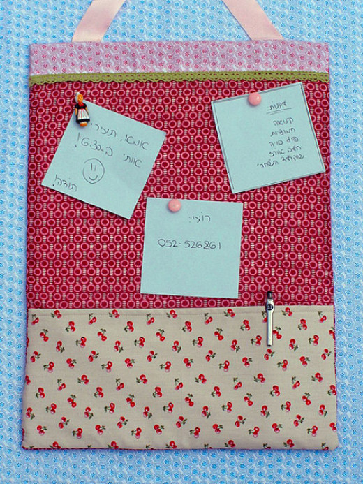 A fabric covered cork board complete with a pocket