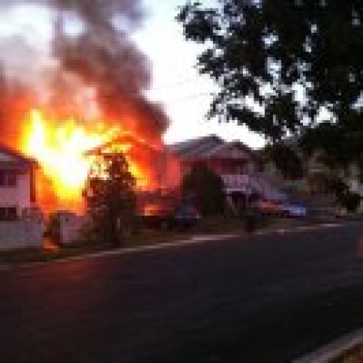 This timber house is burning fiercely nearby, and this time the owner has been lucky to escape alive and unhurt we have been told, because he was awake when the fire started.