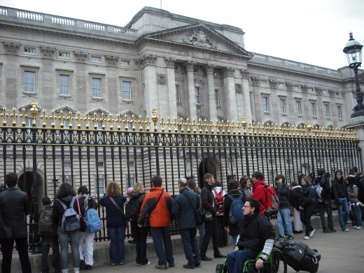 Tourists outside Buckingham Palace in London, UK.  Cities such as London generate enormous amounts of income from the tourist industry.  European countries generally have the infrastructure to cope with high numbers, some poorer countries struggle.