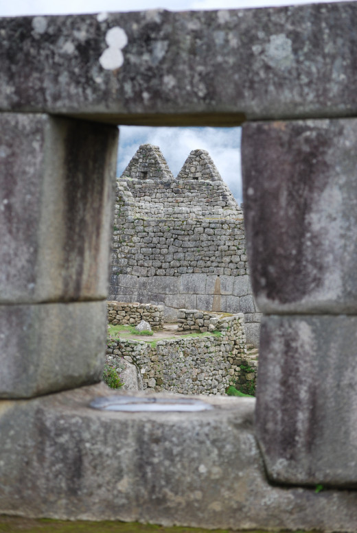 In this image the window in the temple is framing the ruins of Machu Pichu in the background.  Because of the framing with the window, the viewer can understand that the photographer was looking out at Machu Pichu from a distance.