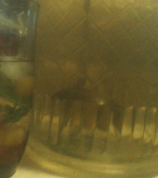 A glass of sun tea garnished with fruit and mint beside a giant glass jar full of sun tea, enough for lots of refills!