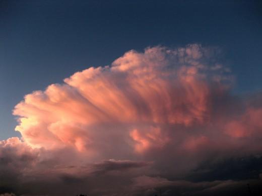 Cumulonimbus anvil cloud lit by the setting sun.