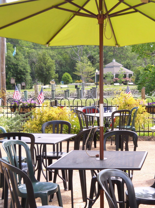 Outdoor seating at Irish Eyes Pub & Restaurant overlooks the Broadkill River and the gazebo in Milton Memorial Park.