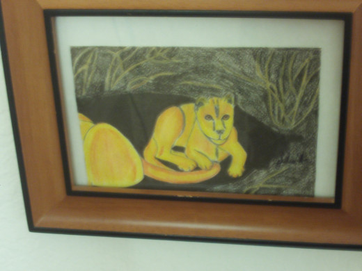 The framed lion drawing is now hanging on the wall.