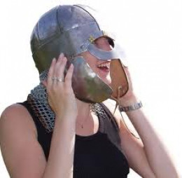 A local girl trying on a Viking warrior's helmet during an open day at the Cumwhitton site