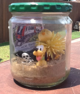 """An example of a """"scrapbook in a jar.""""  A German train ticket, a pluto dog (Disneyland Paris), a pirate flag and a duck (our favorite meal was french duck leg confit)"""