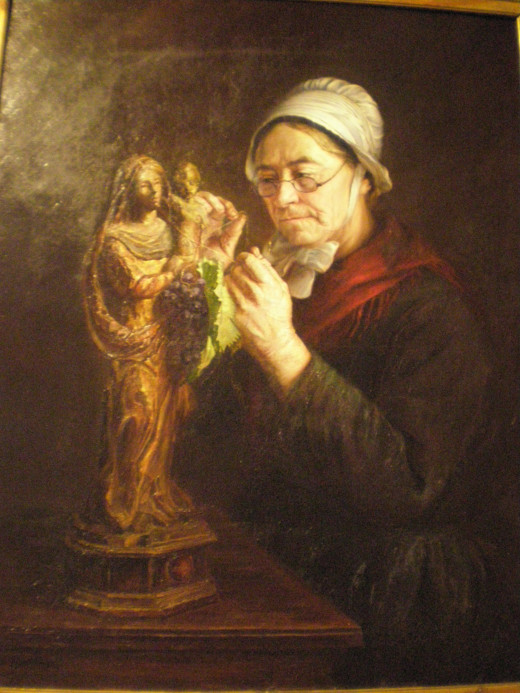 The painting of an old lady tying a bunch of grapes to a Madonna's statue for a holiday. The Madonna with the vine is an image commonly seen in the region.
