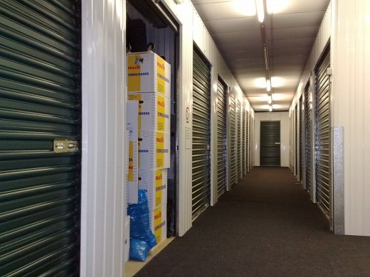 Corridor with self-storage units. Indoor self storage units are best, but they are more costly. I use outdoor self storage units that are very close to where I live. They are cheap and very efficient.