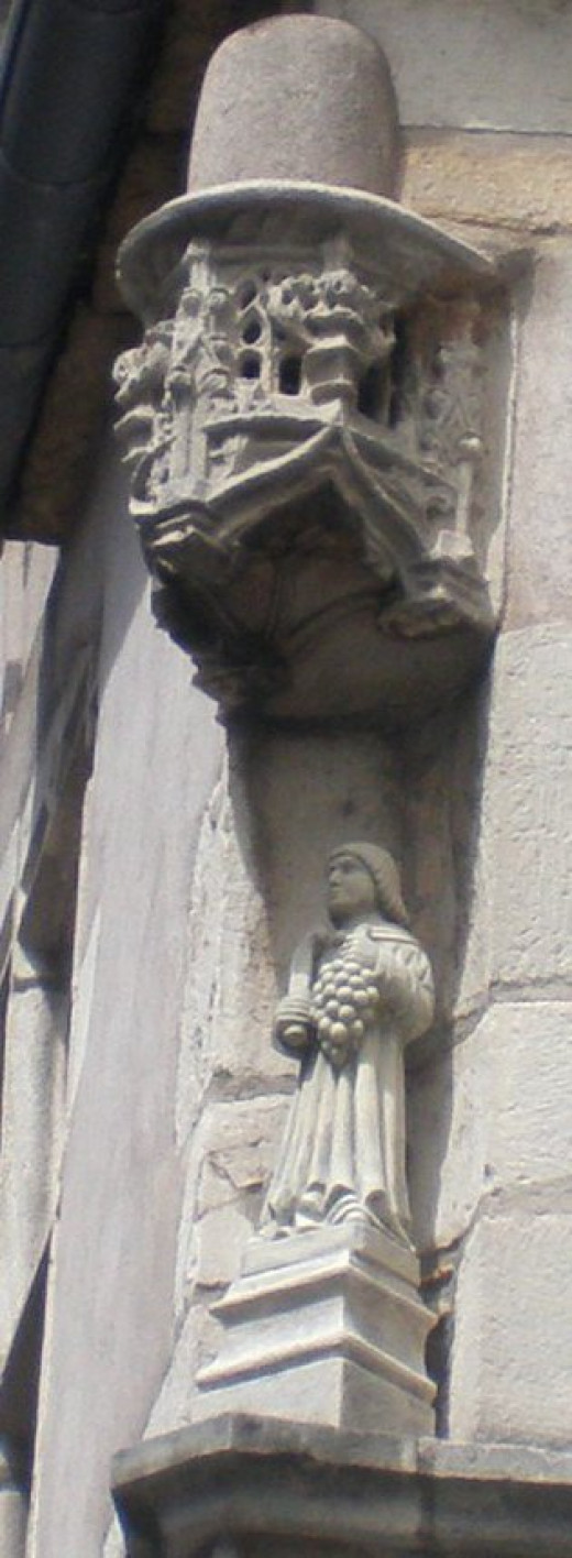 Carving on a house: the patron saint of the vine with a pruning knife.