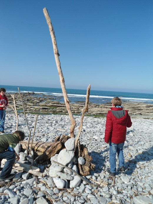 "children working on a ""sculpture"" made of sticks brought by the tides"