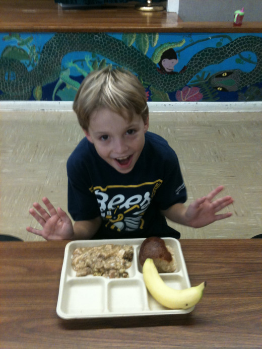 A happy student, enjoying a fully compostable meal on a paper tray.