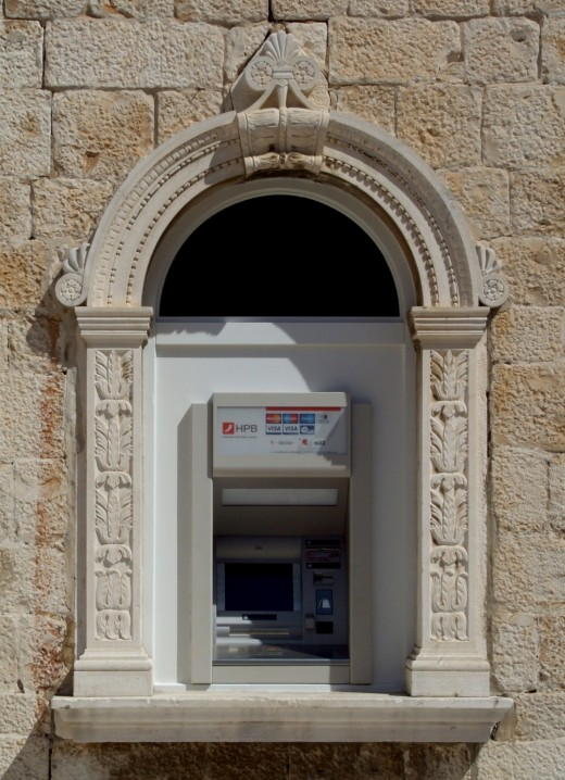 An automated teller machine (ATM) in an old town square in Trogir, Croatia.  Why wait in long bank lines for cash when you can get your money from an automated teller 24/7?