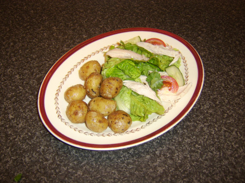 Poached and cooled chicken is served with traditional salad ingredients and cold, minted new potatoes
