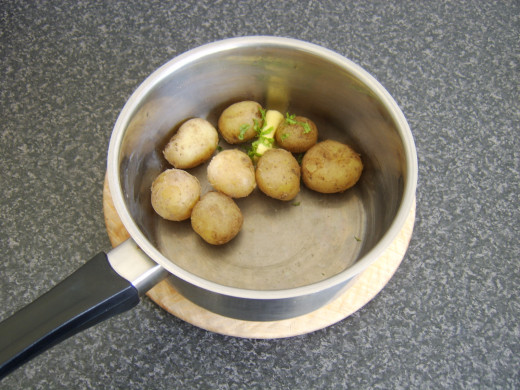 Butter and mint is added to the cooked and drained potatoes