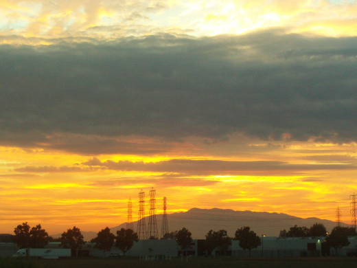 Gray tinged clouds add dimension and interest to the orange tinged sunset with Mount Baldy in the distance.