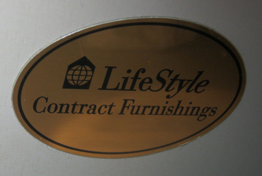 A sticker from inside of the nightstand showing the name of a hotel furniture supplier.