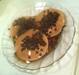 This is a picture of pancakes sprinkled with mini chocolate chips and covered in maple syrup just before going into the microwave.
