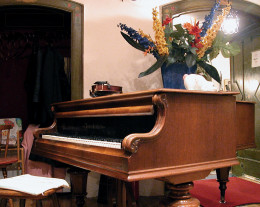 An ordinary baby grand piano in a home setting.