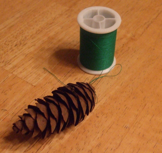 Thread slips under scales at the top of the clean pine cone.