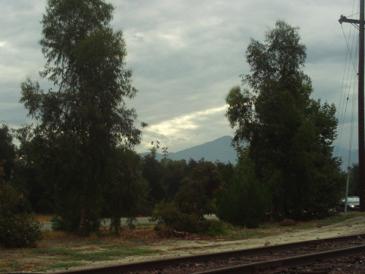 Mount San Gorgonio in the distance with clouds overhead, and the Santa Fe Railroad tracks in the foreground.