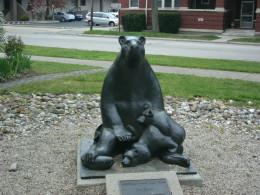 A cute mother bear statue in a garden near main street.