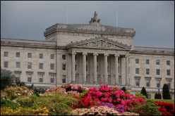 Parliament Buildings, Stormont, Belfast. Part of the front of the building with the main entrance (under the portico) hidden by the rhododendrons.
