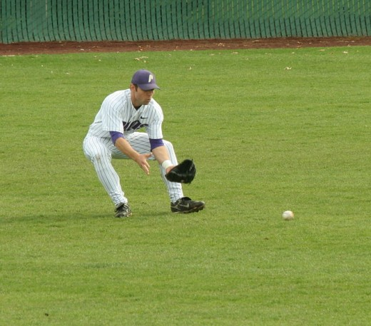 An outfielder getting ready to field a ground ball
