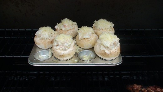 Stuffed mushrooms sitting in a small cup muffin tray on the top rack of the barbecue.