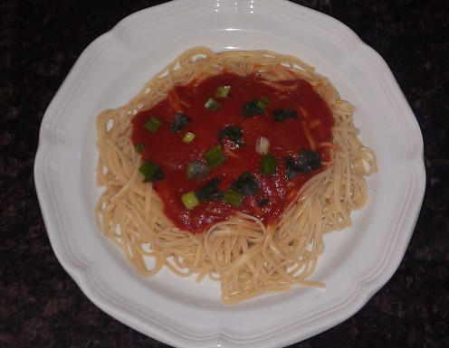 Spaghetti with tomato sauce garnished with basil and scallions that were stored in the freezer
