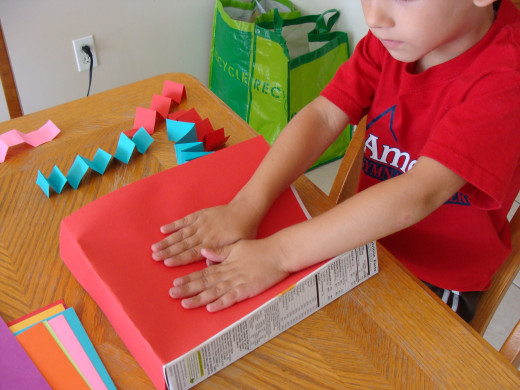 Alex carefully glues down his construction paper on all sides of the box.