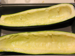 Decored and scooped out zucchini halves.