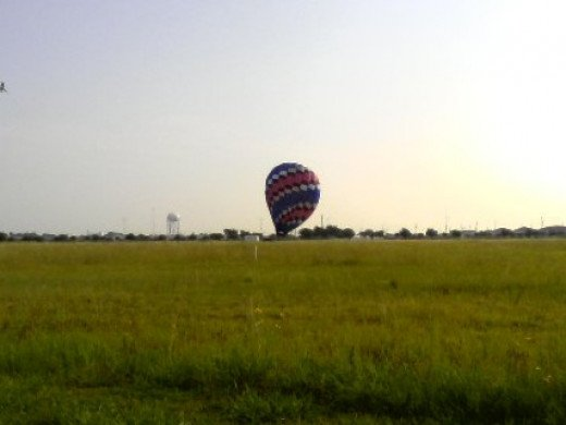 A combination of removing the heat, allowing the air molecules to condense, and allowing some of the air mass to escape out the top, brings the balloon down to earth.