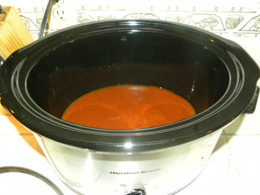 Pour Enchilada Sauce in crock pot, set to low.