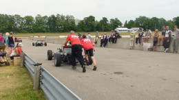 Giving the formula one car and driver a push towards the track.