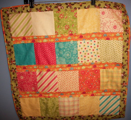 A simple quilt made from a charm pack and strips from fat quarters.