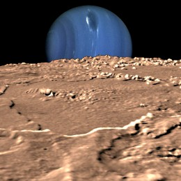 The gas giant planet Neptune rises above the horizon of its moon Triton