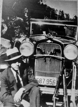 "Gangster Clyde Barrow with a Model A Ford car. Barrow and his accomplice were named ""Bonnie and Clyde""."