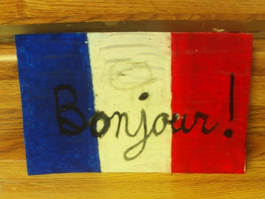 Finish coloring in the red vertical stripe with an oil pastel, and use a black oil pastel to write bonjour on the front of the card.