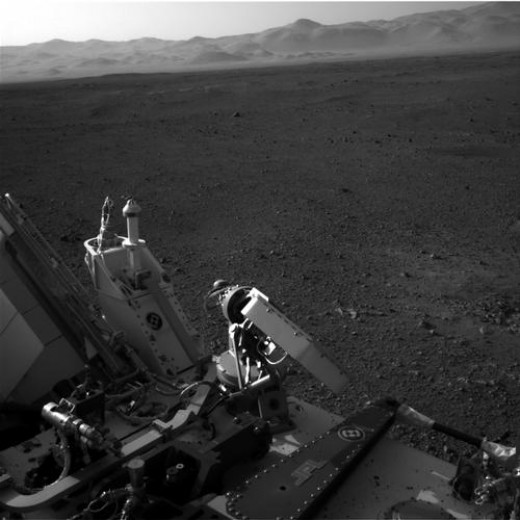 High-gain antenna in foreground, rim of Gale Crater in background.