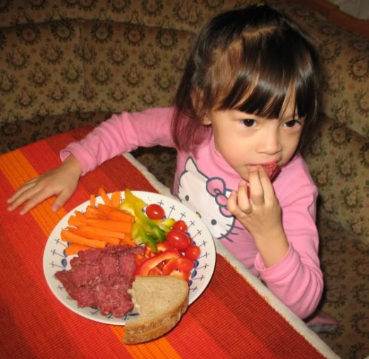 Little girl enjoying a plate of vegetables.