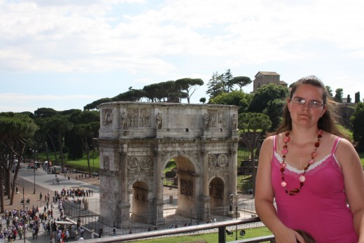 Standing inside the Colosseum with a view of the Arch of Constantine