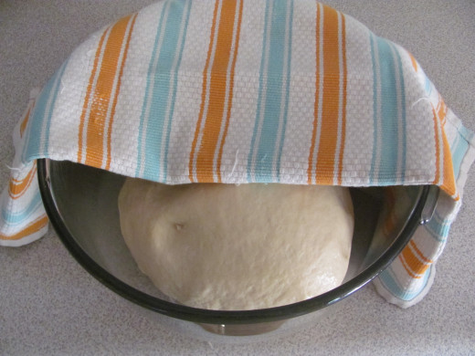 dough placed in buttered bowl and covered with tea towel for rising
