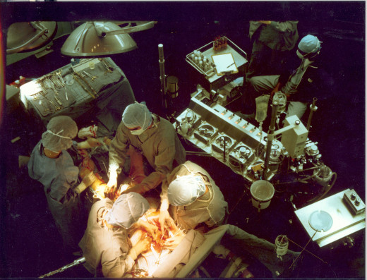 CABG surgery showing the heart-lung bypass machine behind the surgeons. The incision in the leg to harvest the graft vein, and the open chest are visible in this photo.