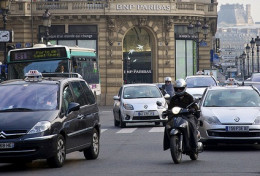Bus, motorcycle and car traffic on the street in front of the Paris Opera