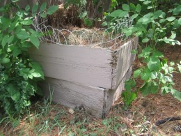 A homemade compost bin made from old boards. I put the spare fencing around the top to help keep any varmints out.