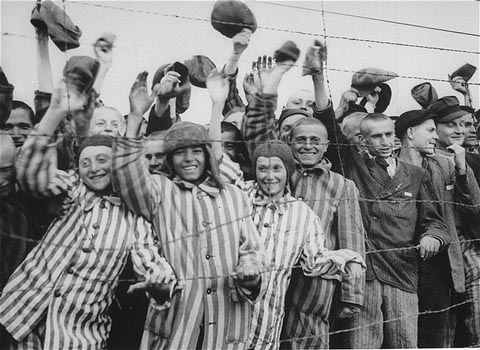 Prisoners at the Dachau concentration camp, waving at Americans after they were liberated