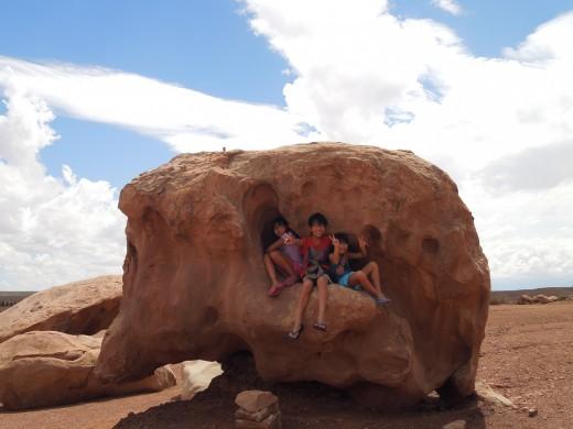 Kids Sitting on A Rock