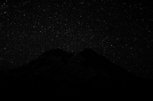 Rainier silhouettes the stars.