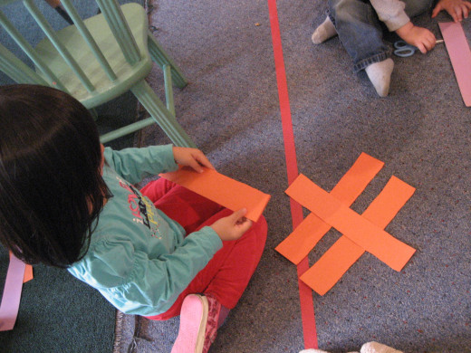 A child uses long and short rectangles to make letters on the floor.