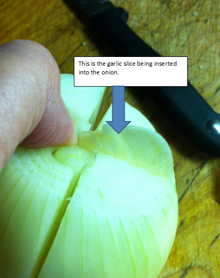 Garlic slice being inserted into onion.